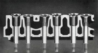 This cross-section through part of the Green Diamond engine block shows the larger water passages which completely surround intake and exhaust-valve ports which facilitate the escape of hot exhaust gasses; the heavy-duty, truck-type valves with full-size stems; and the hardened exhaust-valve seat inserts.